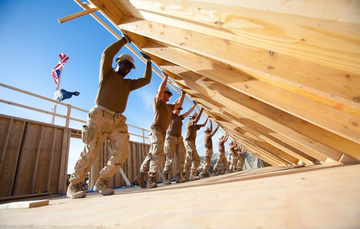 Picture depicts people working together to raise the walls of a home