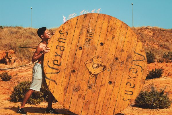 A man doing hard work pushing a huge wooden wheel